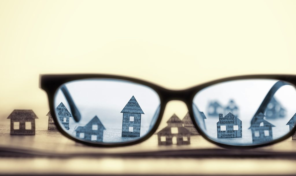Lens of glasses showing houses